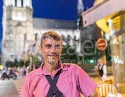 Happy male tourist in 40s enjoying Paris city life at night