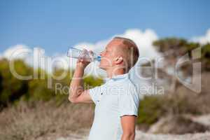 young man ist drinking water summertime dune beach sky
