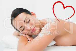 Composite image of peaceful brunette lying with salt scrub on sh
