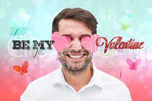 Composite image of handsome man with hearts over his eyes