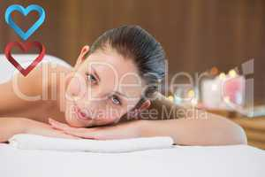 Composite image of beautiful woman lying on massage table at spa
