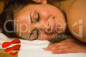 Composite image of happy brunette lying in a sauna