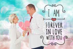 Composite image of older affectionate couple holding pink heart