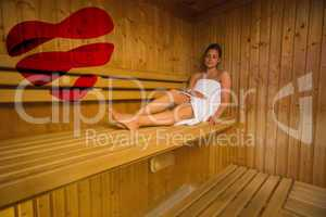 Composite image of calm brunette relaxing in a sauna