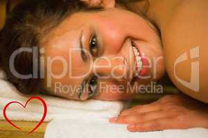 Composite image of happy brunette lying in a sauna looking at ca
