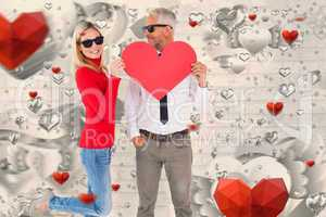Composite image of cool couple holding a red heart together