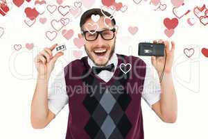Composite image of geeky hipster holding a retro tape cassette p