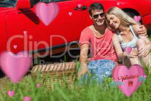 Composite image of smiling couple sitting on the grass having pi