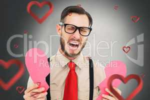 Composite image of geeky hipster crying and holding broken heart