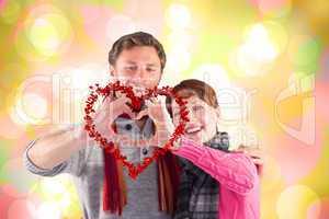 Composite image of couple making a heart shape