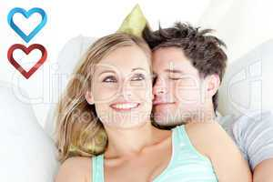 Composite image of portrait of a hugging couple sitting on a sof