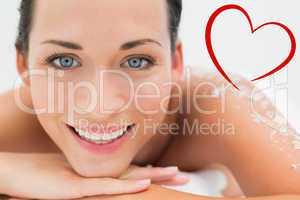 Composite image of peaceful brunette lying with salt scrub on ba