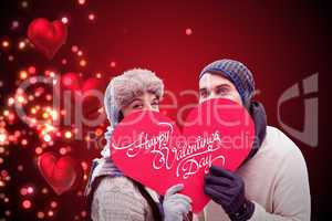 Composite image of attractive young couple in warm clothes holdi