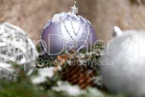 Silver Christmas bauble on a tree with snow