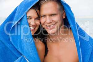 Cheerful couple with a towel covering their heads