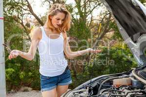 Woman inspecting her car engine after a breakdown