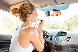 Beautiful woman applying makeup in the car