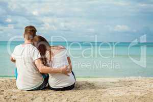 romantic young couple sitting on the beach in summer
