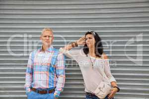 Fashionable couple posing in front of a metal door