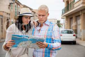Young couple of tourists consulting a map