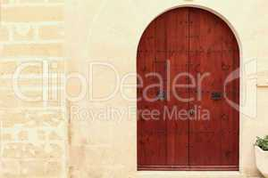 Arched wooden door in a stone wall