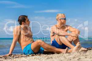 Two handsome young men chatting on a beach