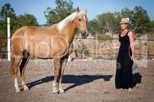 young woman training horse outside in summer