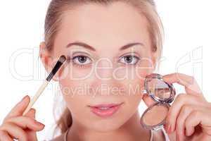 young beautiful woman applying eyeshadow on eyes