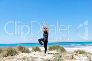 man doing pilates exercises on beach in summer