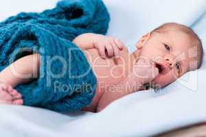 Small infant wrapped in knitted fabric