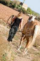 young woman walking a road with horse