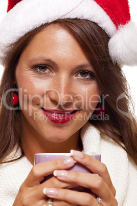 Cold young woman in a Santa hat sipping coffee tea