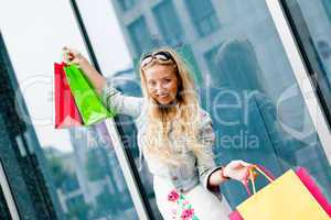 smiling blonde woman with colorful bags on shopping tour