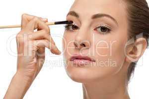 doing the makeup brown eyeshadow on beautiful eyes