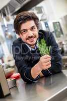 Chef checking the freshness of a bunch of herbs