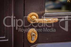Brass door handle on a colorful blue door