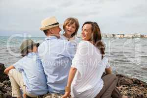 happy family sitting on rock and watching the ocean waves