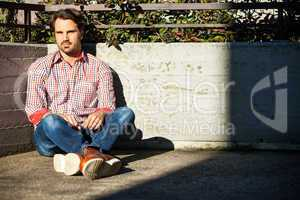 Man sitting on the ground with feet crossed