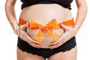 Pregnant woman wearing a bow on her belly