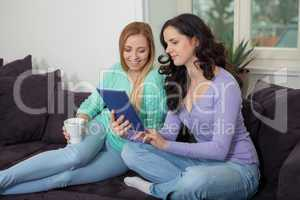 two young attractive girl with tablett pc on couch