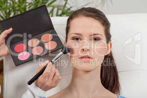 apllying powder rouge make up on face portrait