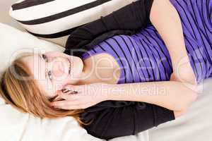 teenager girl smiling and lying on couch with mobile phone