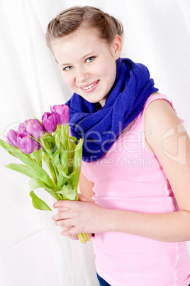 smiling teenager girl with pink tulips bouquet