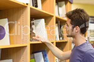 University student choosing books on bookshelves