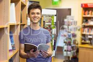Smiling university student holding textbook