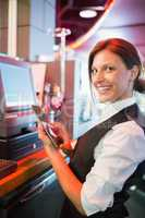 Pretty barmaid using touchscreen till