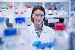 Smiling chemist wearing safety glasses and using tablet pc