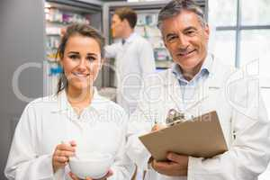 Junior pharmacist mixing a medicine with her senior