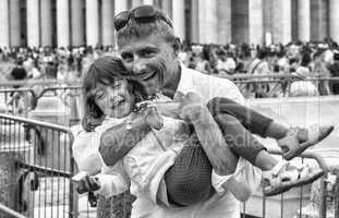Baby girl smiling in father's arms. City life and family concept