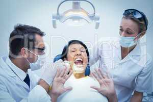 Male dentist with assistant examining womans teeth